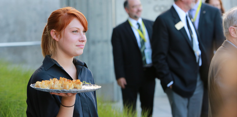 Catering server carrying a tray of food.