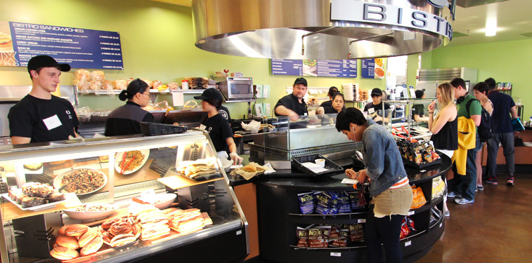 A person filling out a sandwich order form in DUX Bistro while an employee waits to take the order.