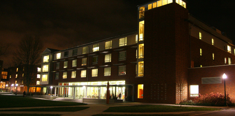 The Living-Learning Center at night with lights on inside.